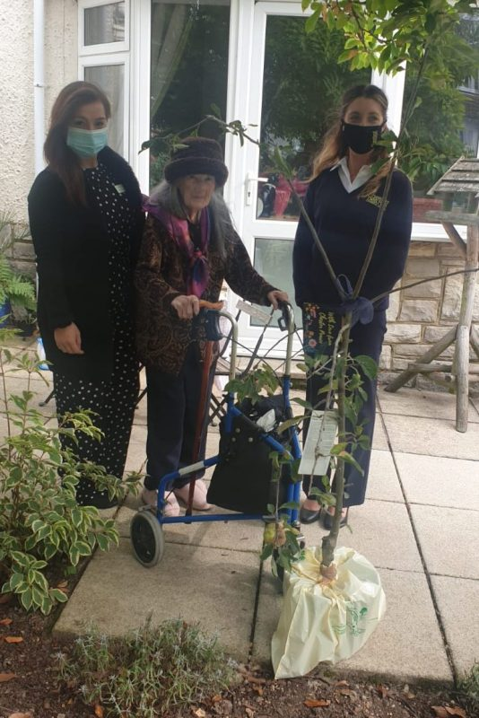 A Blenheim Care Home team member and resident receive an apple tree from Chester Pearce